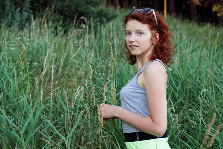 kinky: Portrait of a curly ginger woman  against height grass