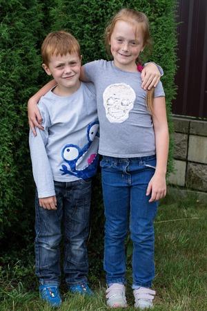 Broer en zus knuffelen elkaar in de tuin