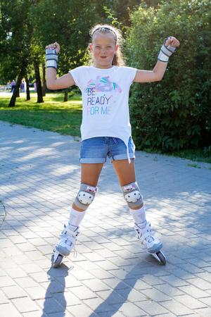 Little smiling girl roller-skating  in the park Stock Photo
