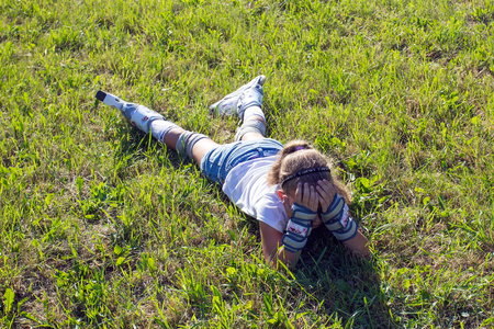 disadvantaged: Little sad girl in rollers is laying on the grass in the park, face is closed by the hands