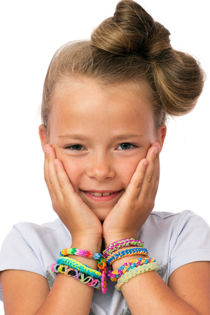 Close up a cute little girl with modern hairstyle and lots of loom bands on the  wrists isolated on white background