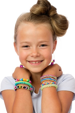 kids weaving: Close up a smiling little girl with modern hairstyle, in earrings and lots of loom bands on the  wrists Stock Photo