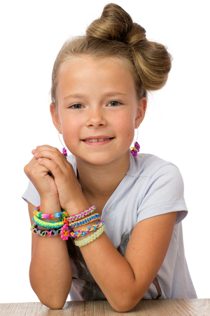 Portrait of  a smiling little girl with modern hairstyle, in earrings and lot's of loom bands on the  wrists, white background Archivio Fotografico