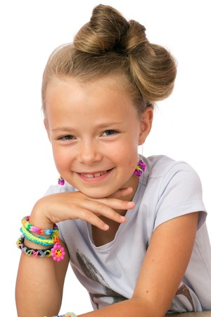 Portrait of  a smiling little girl with modern hairstyle, in earrings and lots of loom bands on the  wrists, white background