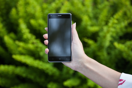 womans hand: Womans hand holding a phone with a large screen against  background of green bushes