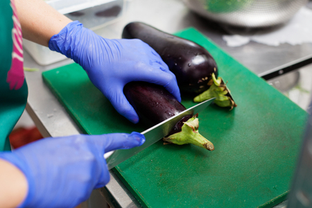 Woman's hands in gloves are cutting eggplants on the board Stockfoto