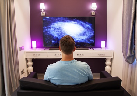 on looker: Man watching 4K TV in the living room, view from the back