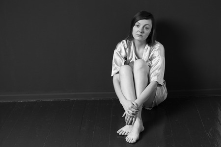 looking in corner: Sad woman sitting in the corner of a room, legs are crossed, looking into camera, black and white Stock Photo