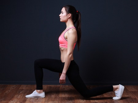 Young fitness woman doing lunge with squats