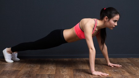 planck: Young  fitness woman doing plank exercise Stock Photo
