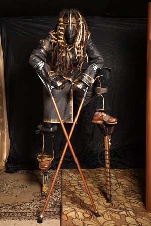 dreadlock: Man in a mask with dreadlocks  on stilts in a cyborg costume against black background