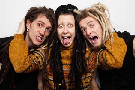freaky: Collective portrait of three freaky people with dreadlocks and piercings aping, white background Stock Photo