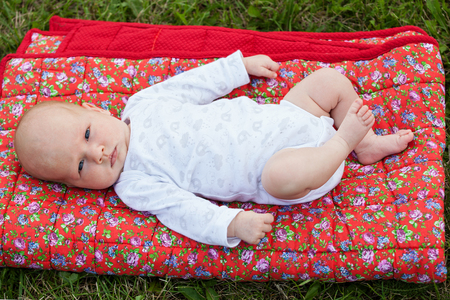 Newborn baby laying on a red blanket on green grass, seriously looking into the camera Stock Photo
