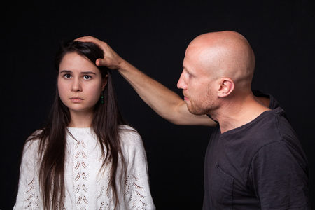 mockery: Domestic violence - man holding hand on womans head, she is looking scared, dark background