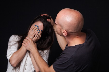 mockery: Domestic violence - man beating the woman, she is closing her face with hands, black background