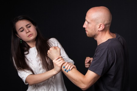 intimidate: Domestic violence - husband  and wife are fighting, woman getting hold of mans fist