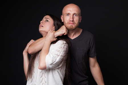 intimidate: Domestic violence - man detaining woman, black background