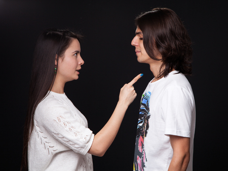 Family quarrel - woman is wagging her finger threatening the man, black background Stock Photo