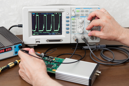 oscillograph: Engineers hands measuring signals on board of the electronic device Stock Photo