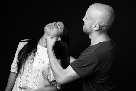 mockery: Domestic violence - an aggressive man  holding a woman by the hair, threatening her,  black and white