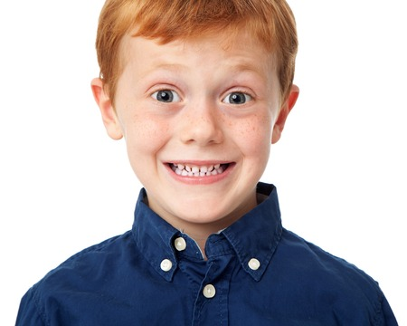 Close up face of a smiling ginger boy isolated on white background Stock Photo