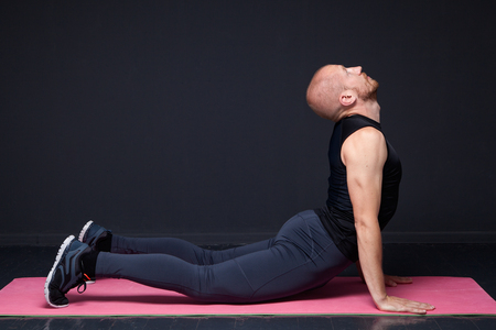 Young fitness man performing cobra pose on the mat Stock Photo