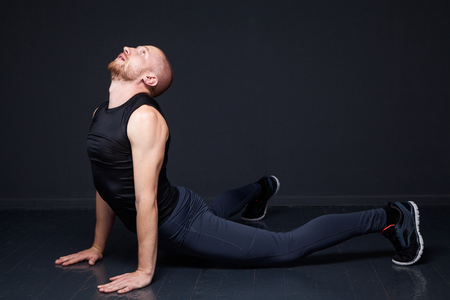 Young athletic man doing pomp exercise against gray wall