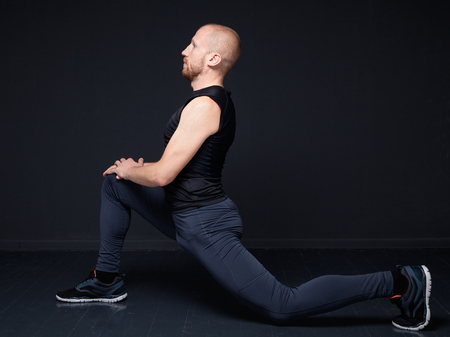 quadriceps: Young fitness man performing stretching of the thigh quadriceps, doing forward lunge Stock Photo