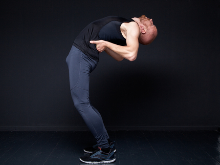 Young fitness man performing backward bend against gray wall
