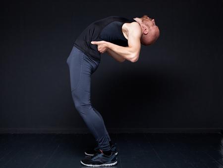 deflection: Young fitness man performing backward bend against gray wall