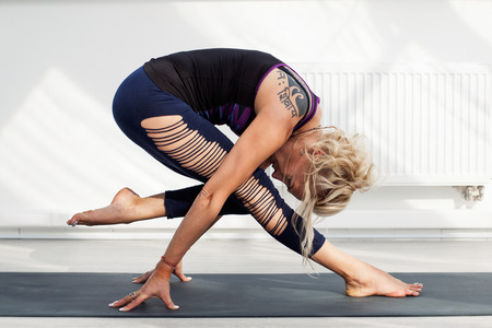 asana: Blonde woman performing yoga asana Stock Photo