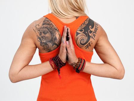 manos unidas: Cierre de la espalda de la mujer con el tatuaje y las manos unidas con los granos aislados en el fondo blanco Foto de archivo