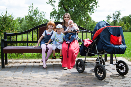 mother on bench: Mother with  three children sitting on the bench in the park Stock Photo