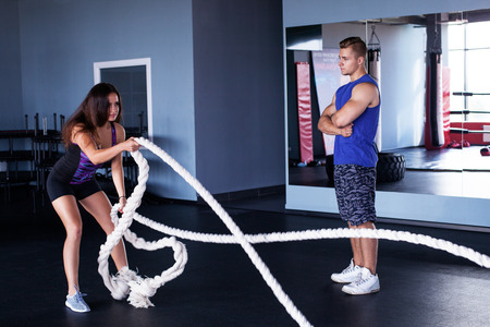 Young woman doing functional training with ropes at the gym Standard-Bild