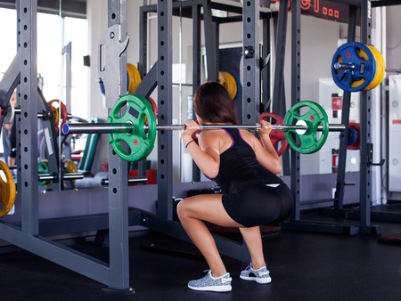 Young athletic woman squatting with a barbell on the shoulders at the gym