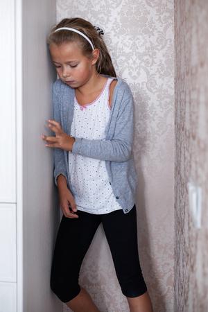 soreness: Little sad girl standing in the corner of the room