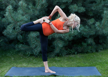 asana: Blonde woman stretching the hip on the mat outdoors