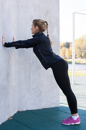 Fitness woman doing push-ups at the wall, back view