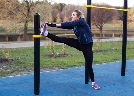 outdoor training: Young fitness woman throwing the foot on the bar and  stretching the  leg outdoors Stock Photo
