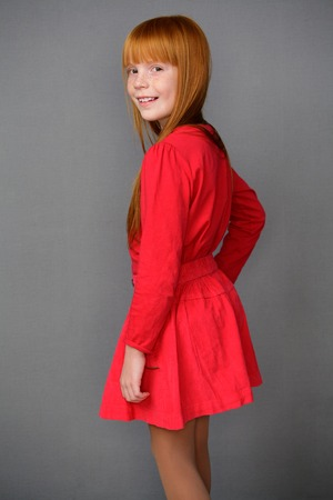 foxy girls: Portrait of a cute ginger girl in a red dress, gray background