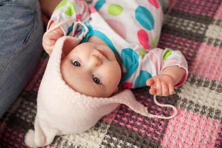 cabeza abajo: El pequeño bebé lindo en un sombrero agradable que pone en el rosa y gris a cuadros al revés Foto de archivo