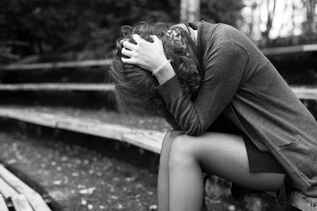 Woman is sitting on the bench in despair, head is in the hands, face is hidden, black and white Stock Photo