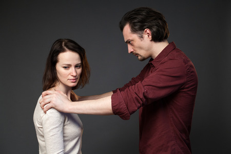 mockery: Family abuse - man is keeping womans shoulders, she is looking to the side, gray background Stock Photo