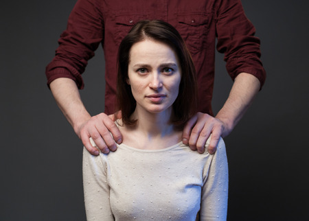 Family abuse - mans hands keeping womans shoulders, gray background Stock Photo