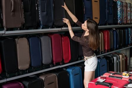 Woman chooses big suitcase at shop Stock Photo