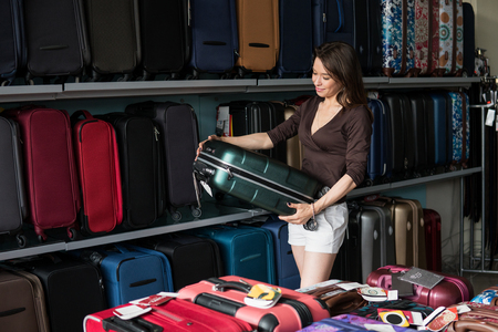 Happy woman chooses big suitcase at shop Stock Photo - 81429666