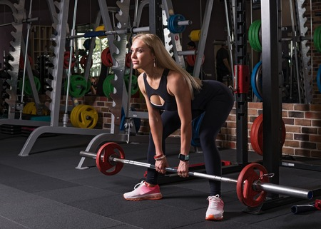 Fitness woman doing a deadlift exercise in the gym