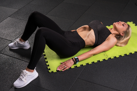 Fitness woman lying and doing a vacuum exercise in the gym