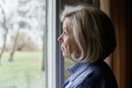 Sad elderly woman looking out the window