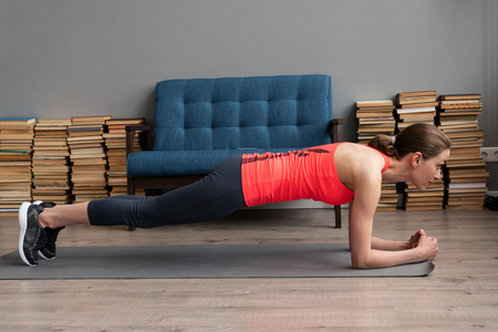Fitness woman doing plank exercise on mat at home